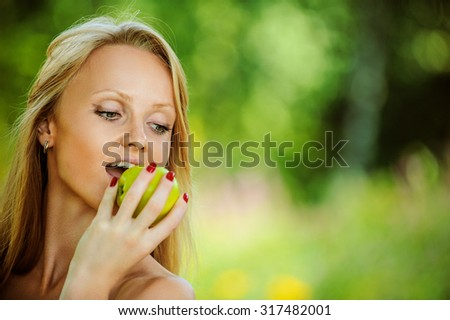 Portrait of beautifu young woman eating apple at summer green park