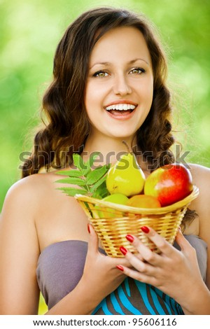 Portrait of beautifu young woman holding a basket of fruit at summer green park