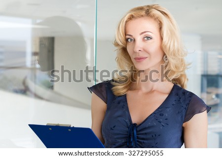 Portrait of beautiful adult business woman standing at her office and holding blue clipping pad with documents. Copyspace - stock photo