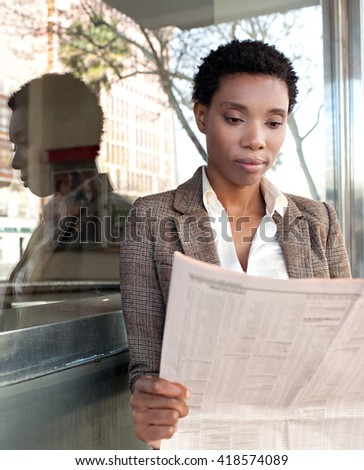 Portrait of beautiful african american business woman reading the financial newspaper stock market by reflective glass office building, sunny outdoors. Professional black woman, finance city exterior. - stock photo