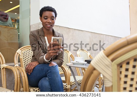 Portrait of beautiful african american business woman sitting at coffee shop terrace drinking coffee using smart phone, city outdoors. Professional black businesswoman lifestyle, exterior. - stock photo