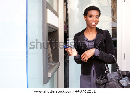 Portrait of beautiful african american business woman smiling holding credit card at bank cash point in the city, outdoors lifestyle. Smiling professional ethnic woman accessing funds in slick bank. - stock photo