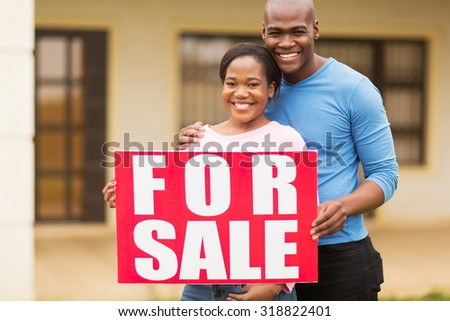 portrait of beautiful african american couple outside home with for sale sign