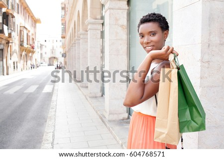 Portrait of beautiful african american female walking in street in old city on holiday, carrying shopping bags, looking smiling outdoors. Black woman consumer, tourist destination, travel lifestyle.