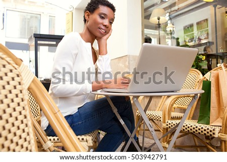 Portrait of beautiful african american professional woman sitting in coffee shop using a laptop computer, working outdoors. Smart black business woman in city, thoughtfully smiling in exterior.
