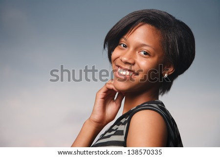 Portrait of beautiful African American teenage girl smiling over blue sky background. - stock photo