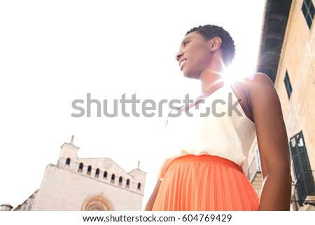Portrait of beautiful african american tourist woman contemplating monument city square, sightseeing on summer holiday with sun rays filtering trough. Smart black female, travel recreation lifestyle.