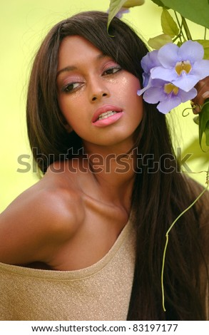 Portrait of beautiful African American woman enjoying spring flowers in the garden - stock photo