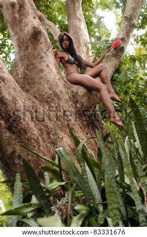Portrait of beautiful African American woman sitting on the tree and enjoying spring flowers in the tropical forest - stock photo