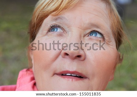 Portrait of beautiful aged woman in the park