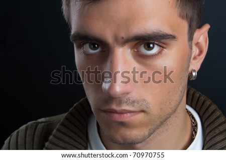 Portrait of beautiful and attractive young man with penetrating eyes and a silver earring in closeup on dark background - stock photo