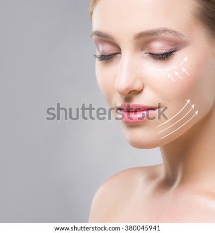 Portrait of beautiful and healthy woman with arrows on her face. Beauty, medicine, plastic surgery and skin care concept. - stock photo