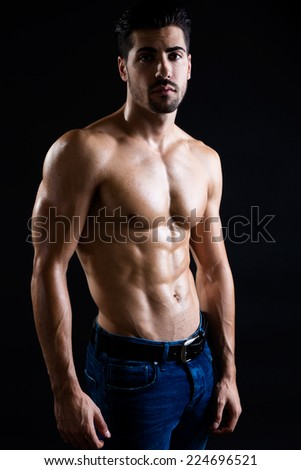 Portrait of beautiful and muscular man in dark background.