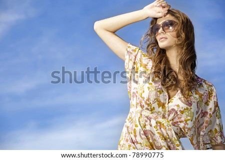 portrait of beautiful and sensuality brunette girl in sunglasses on background blue sky. copy space - stock photo