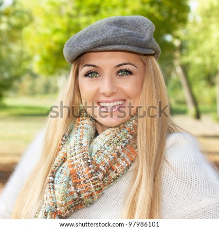 Portrait of beautiful and smiling blond woman  in the park. - stock photo