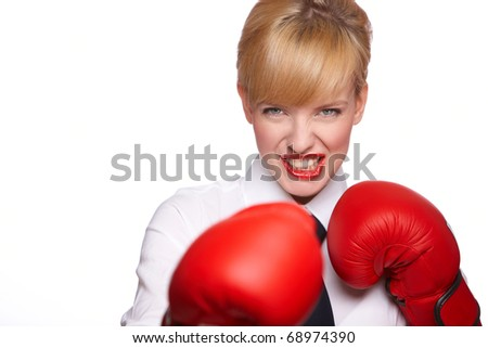 Portrait of beautiful and young business woman wearing boxing gloves - stock photo