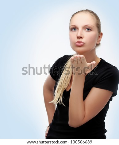 Portrait of beautiful and  young girl wearing black top, sending a kiss at the camera. - stock photo