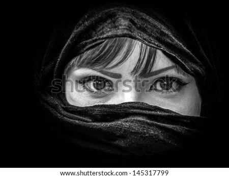 Portrait of beautiful Arab woman with brown eyes wearing black scarf in black and white - stock photo