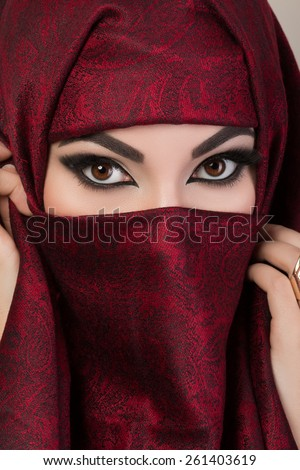 Portrait of beautiful arabian girl hiding her face behind red niqab with paisley ornament - stock photo