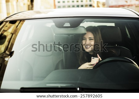 Portrait of beautiful asian brunette young woman holding in hands cell mobile phone inside new car through transparent window background Copy space for inscription Taxi Girl call customer Empty place - stock photo