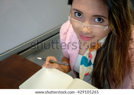 Portrait of beautiful asian college girl student sitting on campus cafe, smile writing notebook
