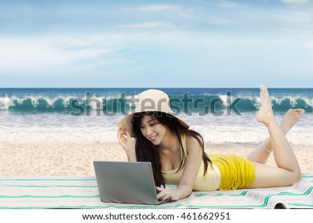 Portrait of beautiful Asian girl lying on the beach while using notebook computer for browsing internet online