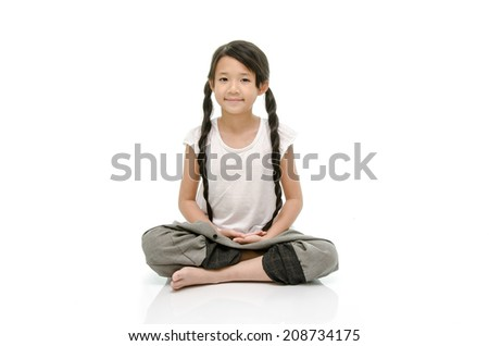 Portrait of beautiful asian girl meditating in pose of lotus in isolation - stock photo