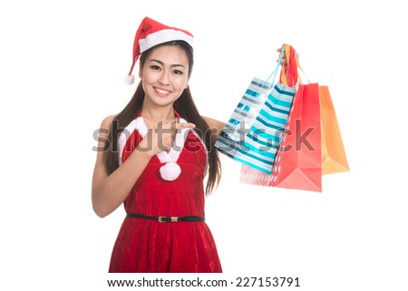 Portrait of beautiful Asian girl wearing Santa Claus clothes, holding colorful shopping bags. - stock photo
