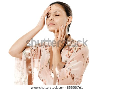 Portrait of beautiful Asian woman applying facial mask with eyes closed in studio isolated on white background - stock photo