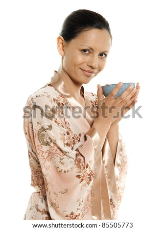 Portrait of beautiful Asian woman drinking tea in studio isolated on white background - stock photo