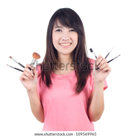 Portrait of beautiful asian woman in casual clothes with makeup brushes on white background - stock photo