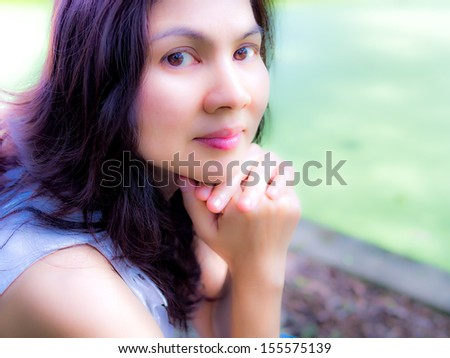 portrait of beautiful asian woman on natural background - stock photo
