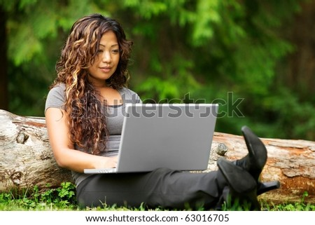 Portrait of beautiful Asian woman using laptop outdoor