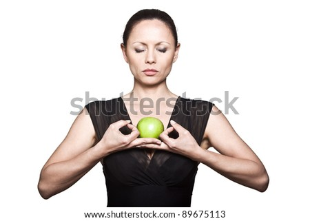 Portrait of beautiful Asian woman with green apple meditating in studio isolated on white background - stock photo