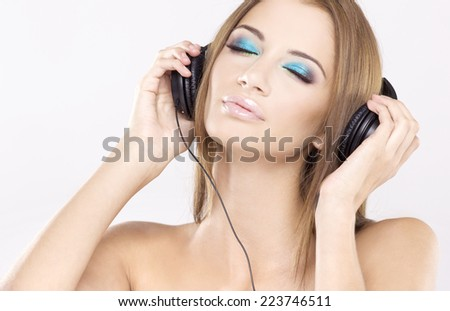 Portrait of beautiful attractive young adult sensuality brunette woman is listen to the music on black headphones - stock photo