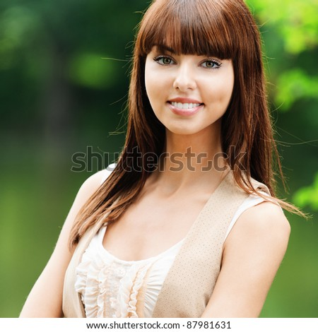 Portrait of beautiful attractive young dark-haired smiling woman wearing beige blouse and waistcoat, standing at summer green park. - stock photo