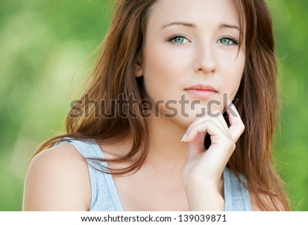 Portrait of beautiful attractive young sad woman has reflected on life at summer green park - stock photo