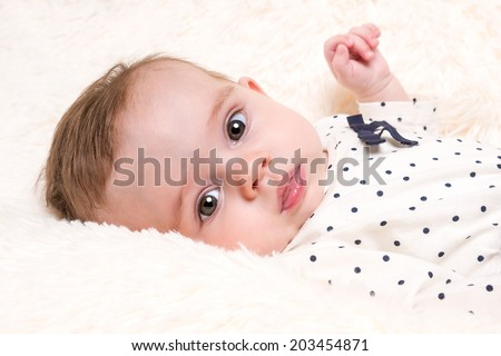 Portrait of Beautiful Baby Girl in Spotty Top resting on Cream Fur Rug