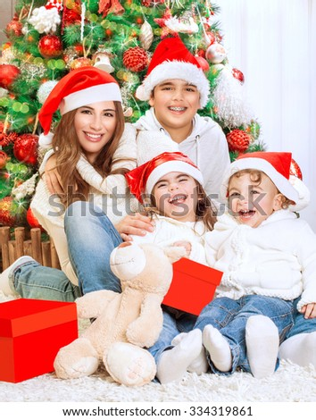 Portrait of beautiful big happy family sitting near beautiful decorated Christmas tree at home, wearing red Santa hats, celebrating winter holidays