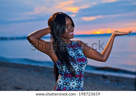 Portrait of beautiful black African American woman posing with open hand palm on the beach at sunset - stock photo