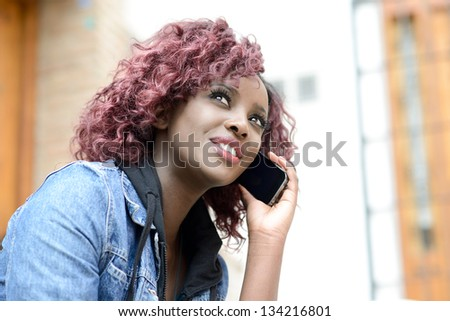 Portrait of beautiful black woman in urban background on the phone - stock photo