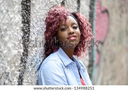 Portrait of beautiful black woman in urban background with red hair - stock photo
