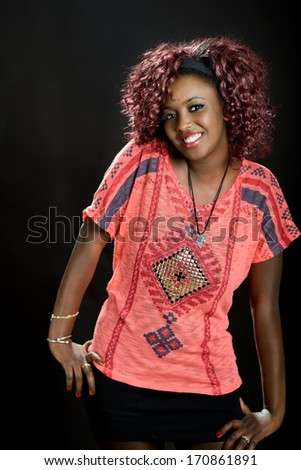 Portrait of beautiful black woman on black background with red hair. Afro hairstyle. Studio shot - stock photo