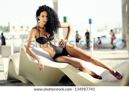 Portrait of beautiful black woman wearing bikini with afro hairstyle - stock photo