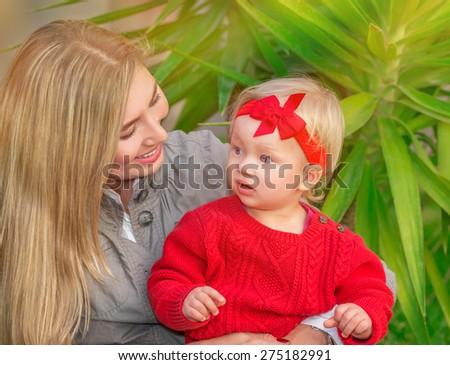 Portrait of beautiful blond female with her little daughter having fun in the park, enjoying motherhood, love and happiness concept - stock photo
