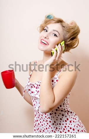 portrait of beautiful blond funny pinup woman with green eyes & curlers speaking on mobile happy smiling & looking at camera - stock photo
