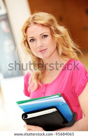 Portrait of beautiful blond girl at university - stock photo