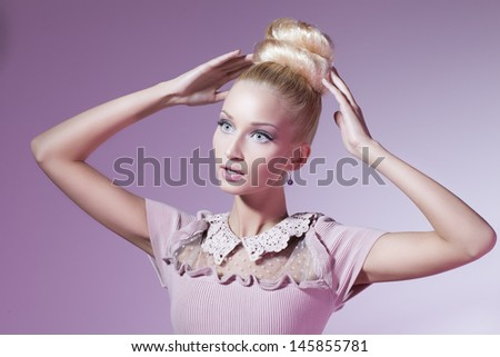 Portrait of beautiful blond girl in pink dress looking like doll over pink background - stock photo