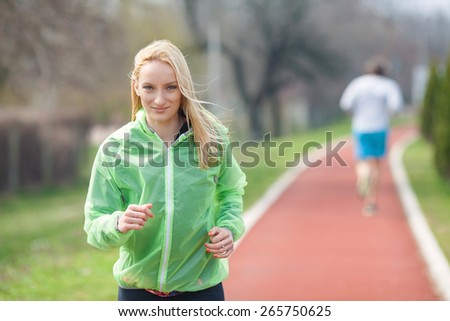 Portrait of beautiful blond girl jogging on running track in a park - stock photo