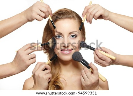 Portrait of beautiful blond girl long wavy, curly hair  with makeup brushes near attractive face, many hands apply make up on woman face isolated on white - stock photo